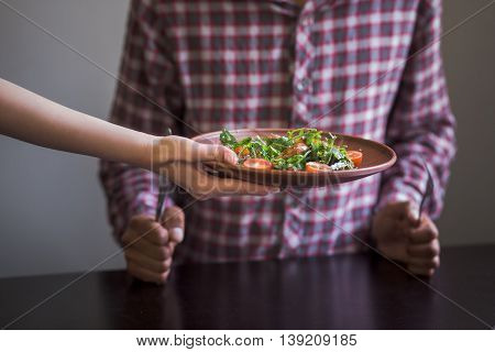 Picture of vegan dish is being served in vegan restaurant or cafe. Man sitting at table and waiting for his order. Vegan and healthy food concepts.
