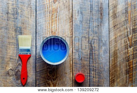 concept preparation for painting with can of blue paint and red brush top view