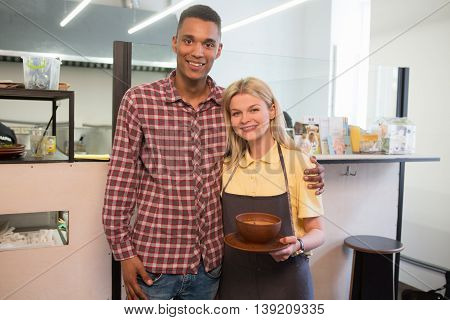 Picture of direstor of vegan restaurant or cafe and his chef loking at camera. Vegan chef woman holding plate with vegan dish.