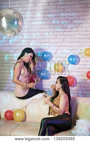 Pretty Vietnamese girls chatting at home party