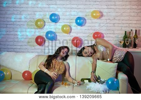 Drunk Asian women sleeping on sofa after party