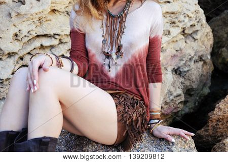 Female neck, chest and hands with boho chic bracelets and leather necklace, outdoor fashion photo with sitting girl on a rock stones