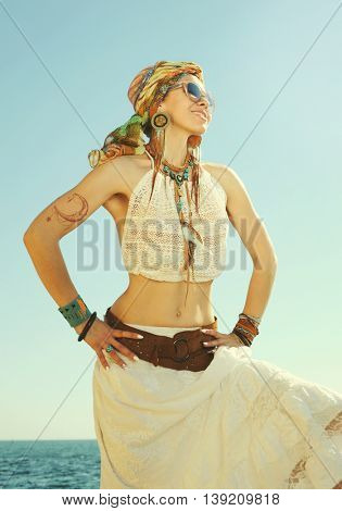 Dressed in boho chic style woman portrait, sunny  outdoor photo against sea. Headband, white lace tank top and skirt, leather belt waist and handmade boho jewelry