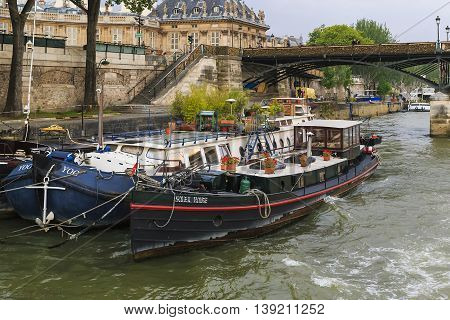 PARIS, FRANCE - MAY 5, 2015: These barges are used by their owners as a floating apartment located in the city center - along the quays of the Seine.