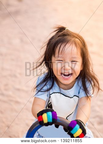 happy Asian child on a seesaw in sunset light