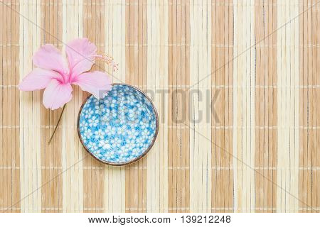 Closeup cute ceramic cup for soup with pink flower on blurred wood mat textured background