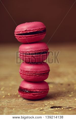 a stack of appetizing red macarons on a rustic wooden surface