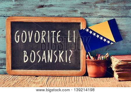 a chalkboard with the question govorite li bosanski?, do you speak Bosnian? written in Bosnian, a pot with pencils, some books and the flag of Bosnia and Herzegovina, on a wooden desk