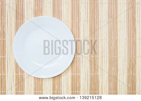 Closeup white ceramic dish on wood mat textured background on dining table in top view with copy space
