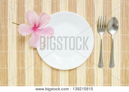 Closeup white ceramic dish with stainless fork and spoon with pink flower on wood mat textured background on dining table in top view
