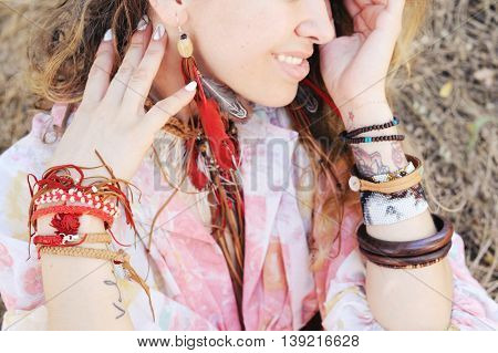 Female neck and hands with boho bracelets and necklace with red feathers and brown leather, outdoor fashion portrait in a forest, soft vintage color tone