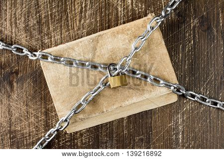 Old book with chain and padlock on wooden background.