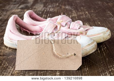 Kids canvas shoes with blank tag on a wooden background