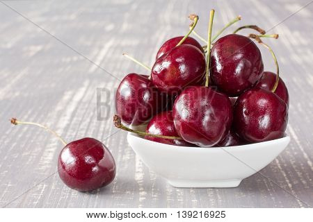 Cherries in white bowl on the grey wooden surface