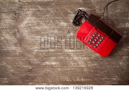 Top view of old fashioned telephone on wooden background with copy-space