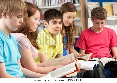 Teenage Students In Library Reading Books
