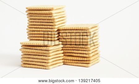 Square crackers lie in piles on a white background