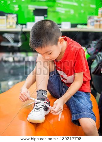 Young Asian boy , action tying shoelace