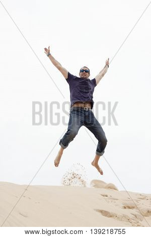 Happy Man With Sunglasses Jumping In The Sand Of A Beach