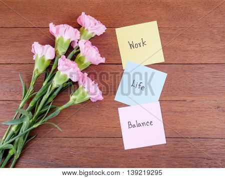 Handwriting word Work Life Balance on notepaper and pink Carnation flower with wood background