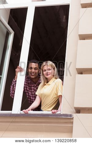 Picture of romantic couple looking from window and smiling for photographer. Happy couple staying in their new apartment or flat.