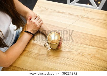 Young girl is sitiing at table and holds cup of coffee