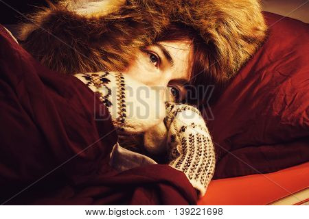 Woman lying in a bed wearing fur hat and mittens and freezing.