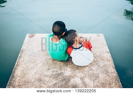 two Asian brothers leaning on each other for support