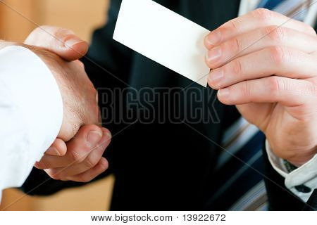 Businessmen having handshake, one handing business card over; only hands to be seen