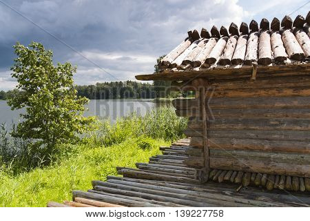 ancient log house on lakes island and cloudy sky