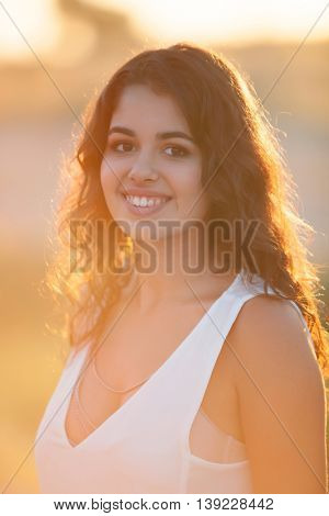 Beauty Sunshine Girl Portrait. Sunny Summer Day under the Hot Sun. Happy Woman Smiling and looking at camera.