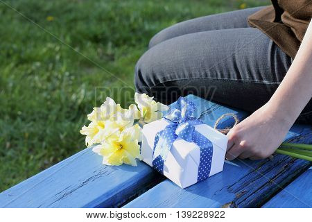 person on a bench with flowers in hand and present