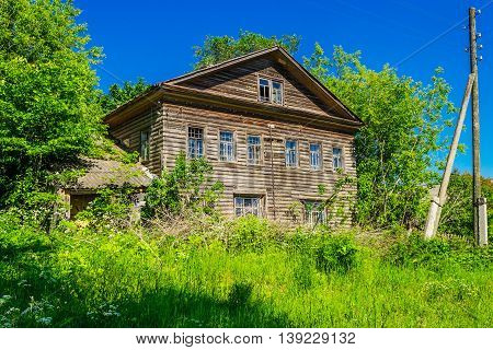 Old wooden house among the trees in summer