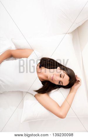 A young, beautiful woman relaxing in the bed at home