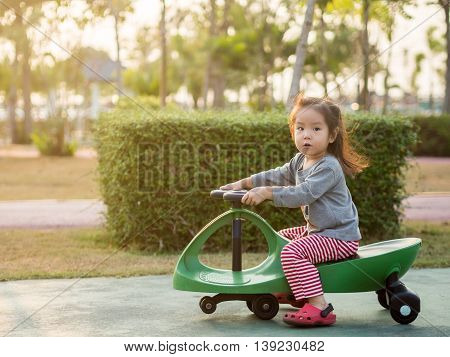 Happy kid asian baby child playing a swing car in the garden