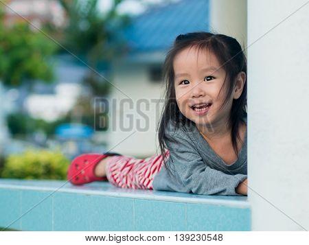 Adorable little girl playing peekaboo asian child