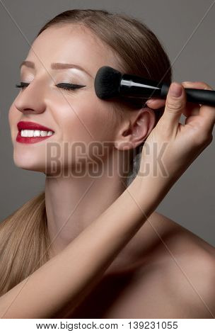 Makeup. Woman Applying Make-up on her Face . Cosmetic Powder Brush for Make up. Perfect Skin.