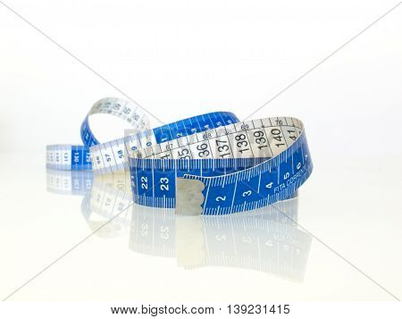 Measuring tape on white background and reflective table