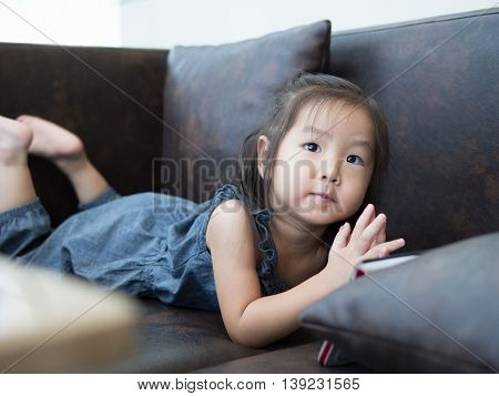 Beautiful young girl child laying down on a sofa at home watching tablet asian girl