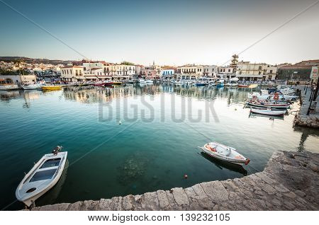 RETHYMNO, CRETE ISLAND, GREECE - JUNE 29, 2016: View of the old venetian port of Rethimno on Crete island, Greece. Tourists relaxing on promenade.