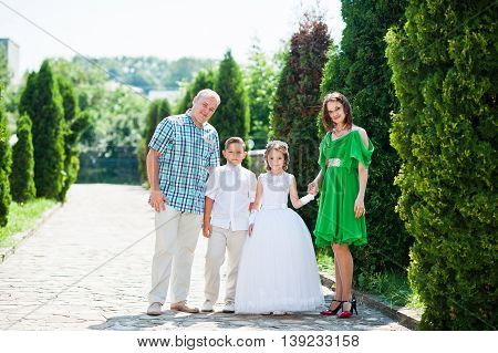Happy Family Stay At Thuja Alley And Looking At Camera