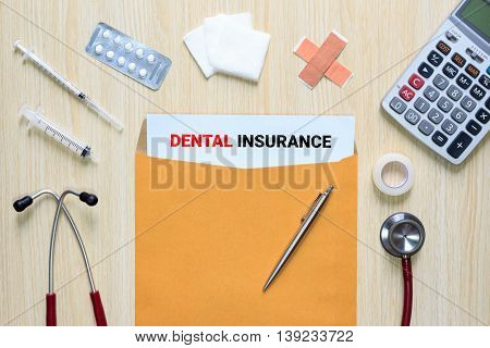 Top view of Dental Insurance with letter envelope stethoscope hypodermic syringe plaster gauze medicine tape and calculator.