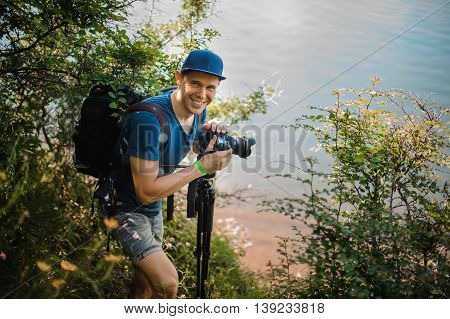 young man in cap holding digital camera outdoor