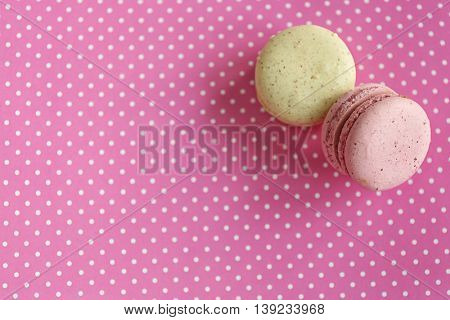 Tasty macaroons on pink spotted background