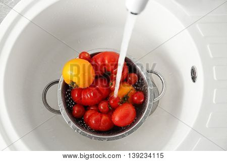 Water flowing into colander with tomatoes in kitchen sink