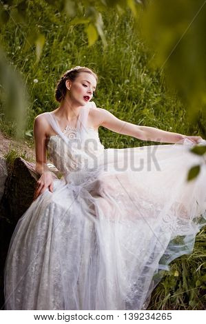 Beautiful girl in a white dress lies on tiptoe . boho style