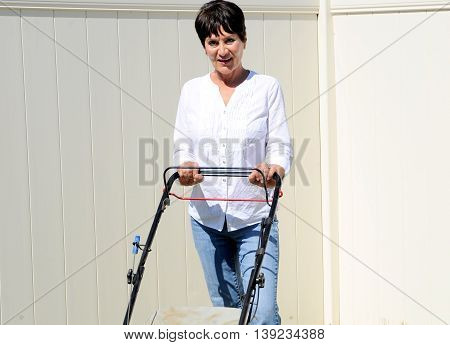 Mature female beauty doing yard work outdoors.