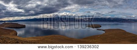 Panorama of lake Baikal and islands. Stormy clouds on the sky