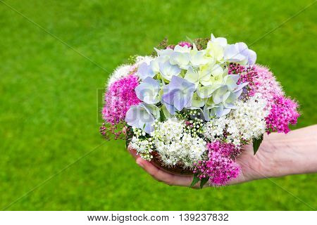 Hand giving bouquet of summer flowers on vase with grass background