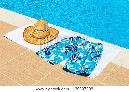 reed hat and swimming trunks on towel near blue fswimming pool